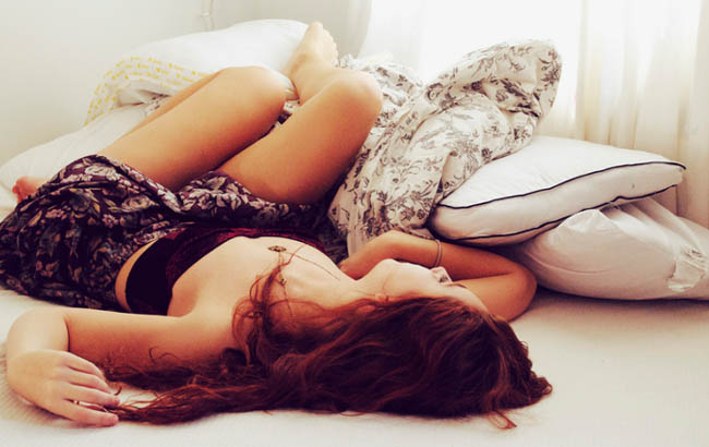 Menina que dorme na cama com capas brancas